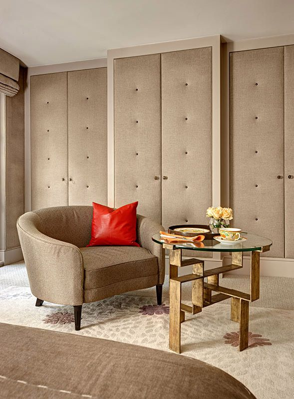 Master bedroom padded fabric buttoned wardrobe doors with club arm chair and unique brass & glass table.