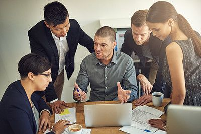 Shot of a group of coworkers discussing something on a laptop during a meeting - stock photo #1361307