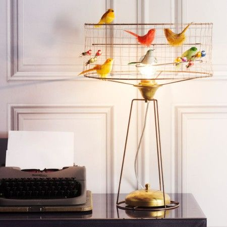 An addition to our bird cage lighting collection this striking and unique table lamp is home to a menagerie of pretty coloured birds made from real feathers. A truly beautiful and eye-catching lamp.