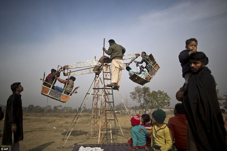 Pakistani Christian children enjoy a ride on a hand-operated Ferris wheel for the price of 10 rupees (approximately 10p)