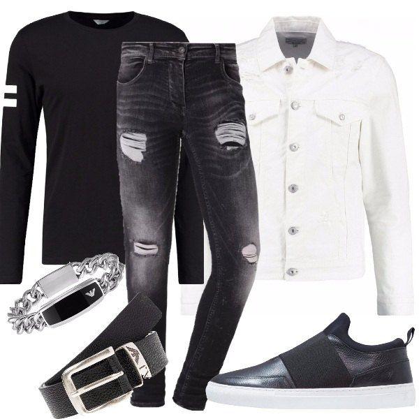 Outfit composto da jeans neri con strappi, giubbotto di jeans bianco, t-shirt nera a maniche lunghe con bande bianche sulle maniche, scarpe nere e cinta e bracciale firmati Armani.