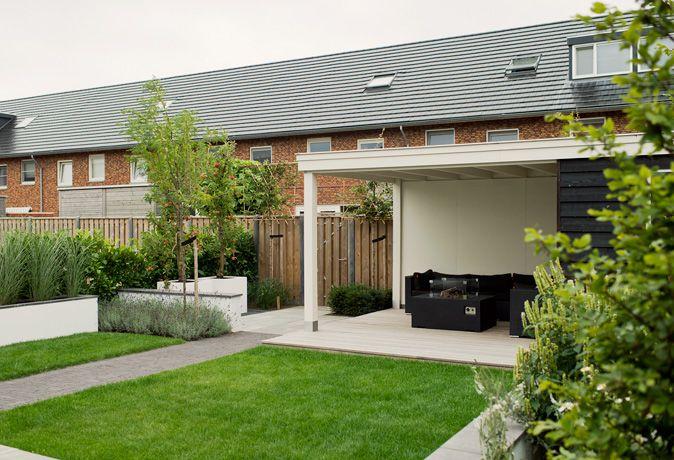 Kindvriendelijke tuin met mooie zichtlijnen in Zwolle. Met gazon, veranda, plantbakken en niveauverschil. www.buytengewoon.nl