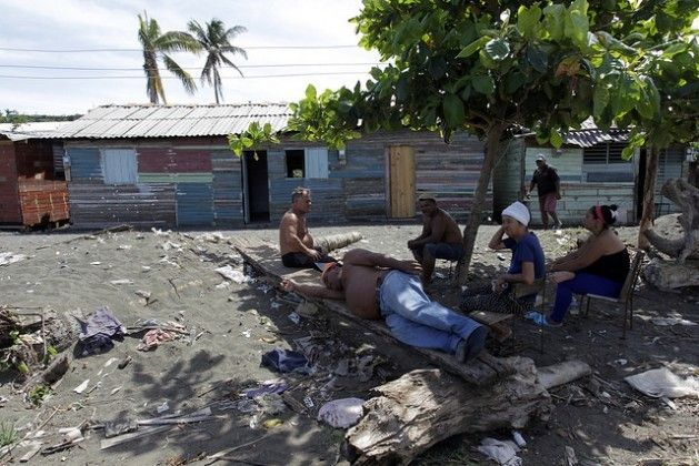"""19 May 17  Local residents of La Playa rest under the shade of a bush on a polluted sandbar or """"tibaracón"""" at the mouth of the Macaguaní River, near the city of Baracoa in eastern Cuba. Credit: Jorge Luis Baños/IPS"""