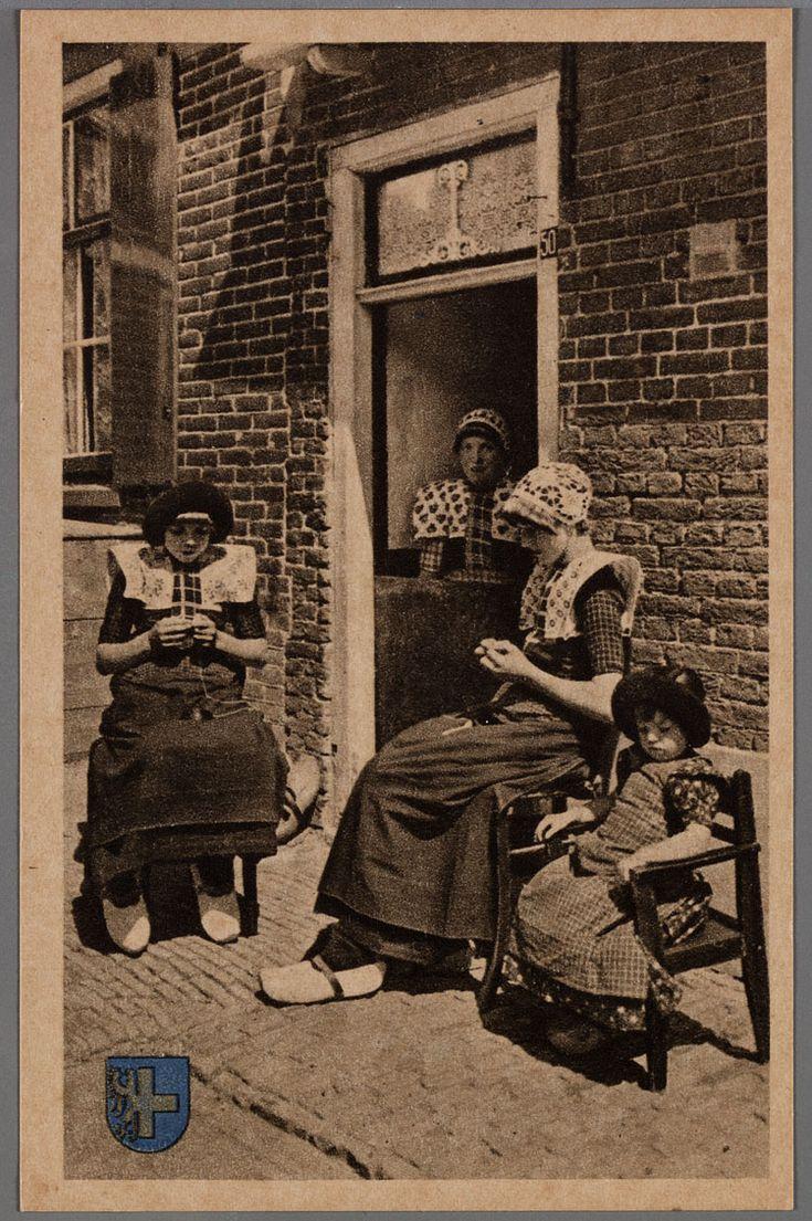Sing staot over de ongerdeur, de deeres kaoken. 1930-1940 Achter de onderdeur een vrouw met gehaakte muts en wit gebloede kraplap. Zittend voor de deur een hakende vrouw met gehaakte muts, witgebloemde kraplap, gedeelde rode doek en donkere boormouwtjes, klompen met een leertje. Twee meisjes met pluummuts, de oudste met kuldfer, kraplap en rode doek, de jongste met jurkje en fries schort. #Utrecht #Spakenburg