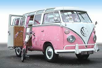 Pink and White Samba VW camper van with matching Raleigh Chopper Bike.