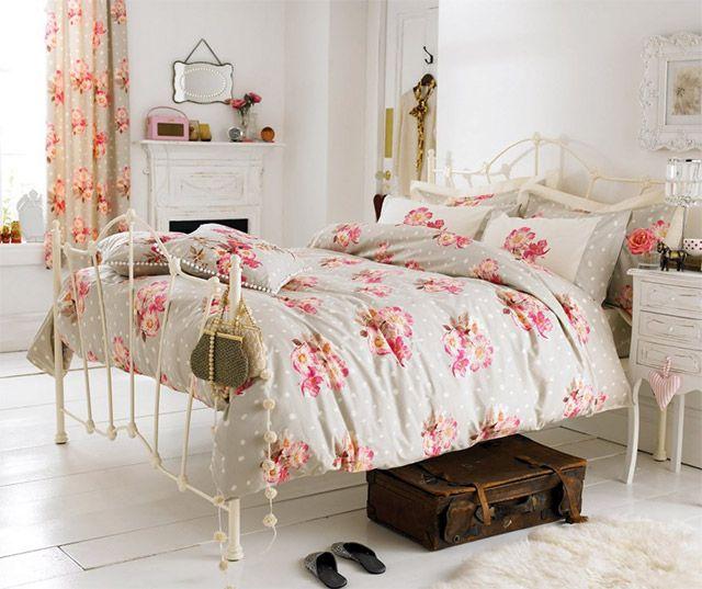 Dormitorio femenino romántico. Cama con dosel blanco con textil de cama en gris con lunares blancos y rosas estampadas. La misma tela la vemos en las cortinas. Bajo la cama una maleta de cuero y alfombra redonda peluda blanca.