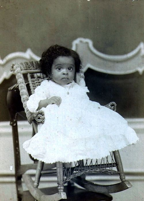 Baby Cakes | The Black Victorians | 1898 Studio portrait of a young African American baby girl dressed in a fancy white dress sitting on a rocking chair. c. 1898