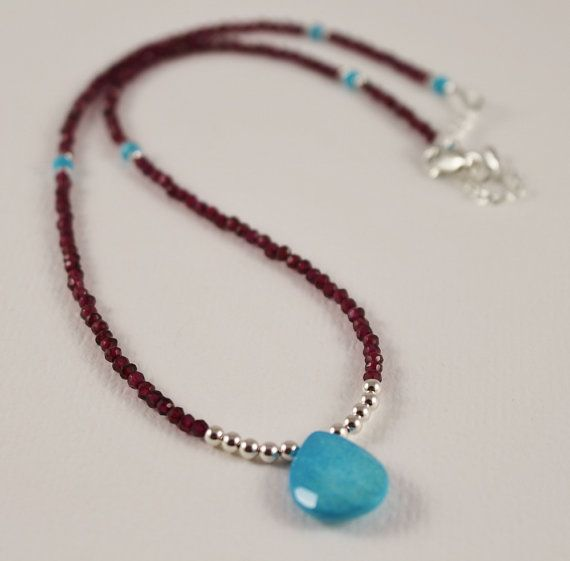 garnet and sleeping beauty turquoise necklace Channel your inner boho-style with this necklace by Tam Davis Designs. A vibrant Sleeping Beauty turquoise drop is covered in a surface of light reflecting facets and centered at the base of a sparkling faceted garnet chain. Sterling