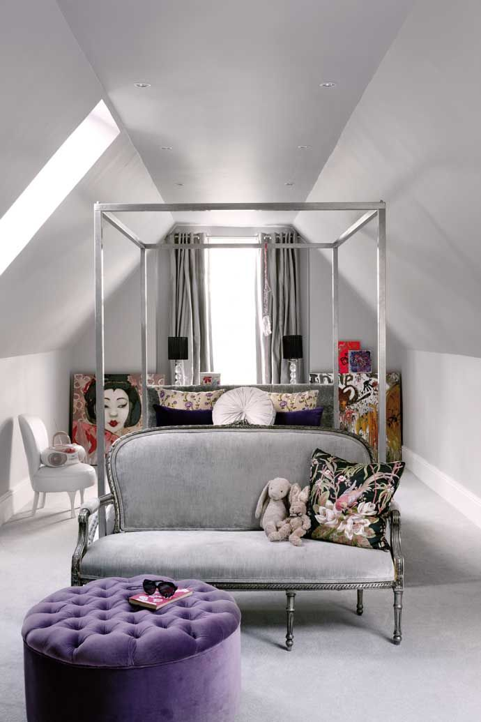 An attic bedroom with a Ralph Lauren four-poster. The sofa and pouffe were found at antique stores.