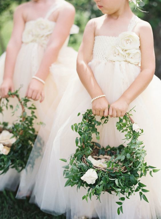 This greenery covered flower girl basket adds a touch of whimsy to any wedding ceremony.