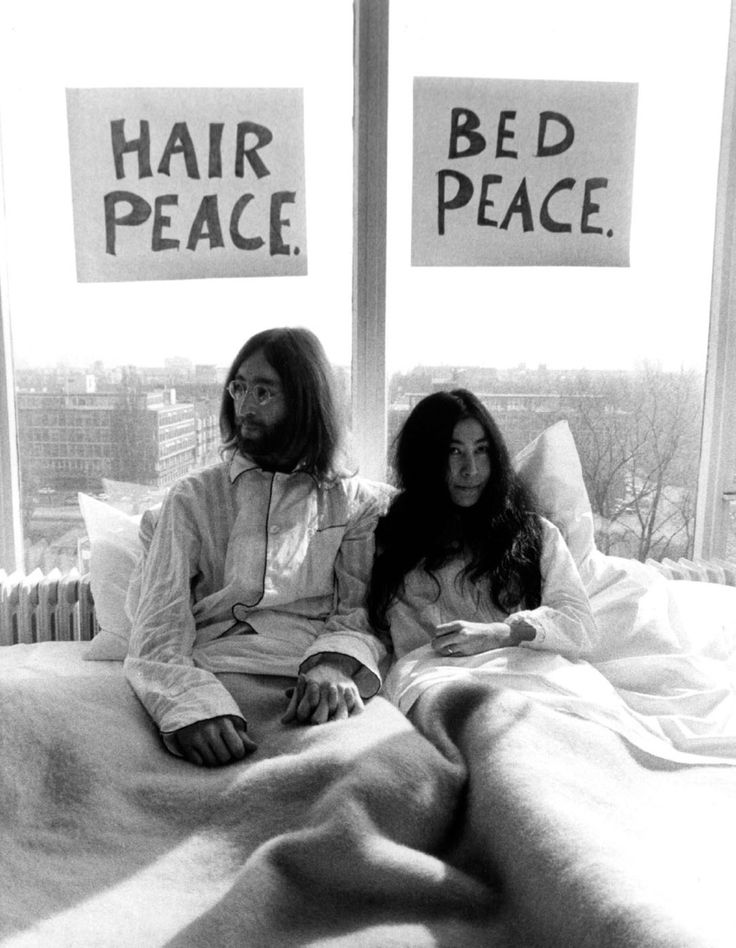 """Beatles legend John Lennon married his second wife Yoko Ono on March 20, 1969. Five days later, in lieu of a traditional honeymoon, the newly-weds holed up in the bed of the Amsterdam Hilton's presidential suite, welcoming the world's press into their hotel room to display their deep opposition to the Vietnam War. This was followed up a couple months later with another bed-in at the Queen Elizabeth Hotel in Montreal, where Lennon and a group of supporters recorded the song """"Give Peace a…"""