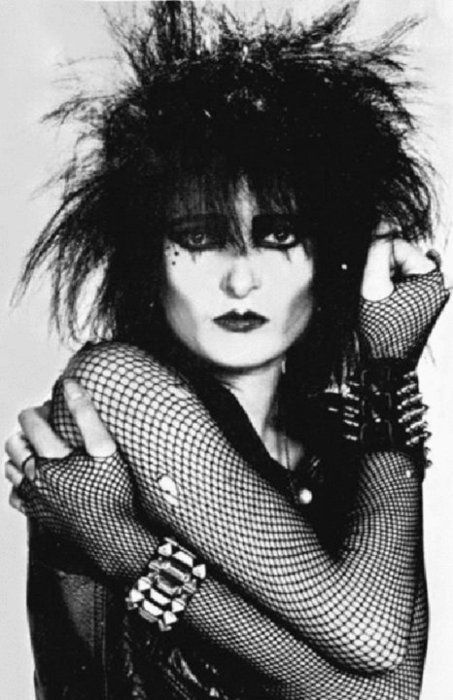 """""""The Ice Queen of Punk"""" Siouxsie Sioux born Susan Janet Ballion in London in 1957 is who is best known as lead singer """"Siouxsie and the Banshees"""" and """"The Creatures"""". Early in Sioux's career she recited poems and prayers to improvised music. Sioux influenced PJ Harvey. Sinead O'Connor and Tracey Thorn. She also influenced the look of Death from Sandman comics"""