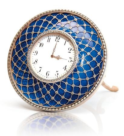This Faberge clock is set in an opaque white enamel sphere with arab numerals and surrounded by an exquisite translucent blue enamel circle in guilloche technique with a golden net work with flowers on the crossings that is one of main characteristics of Faberge's work. Surrounding the dial there are half seed pearls and around the outer circle a series of laurel leaves set on red enamel.