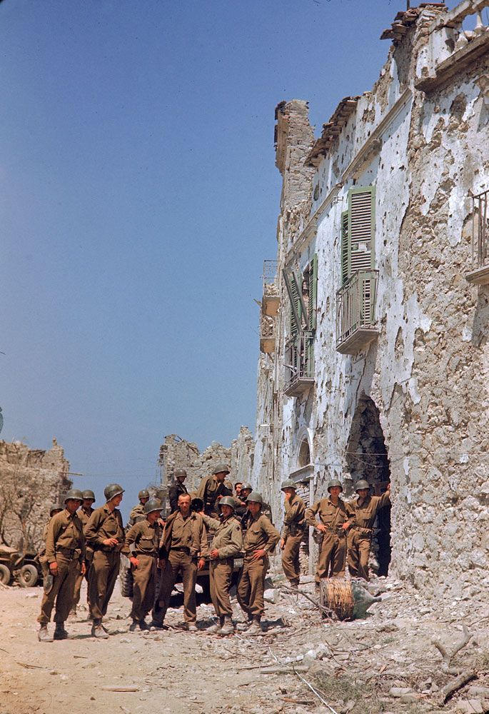 American troops, somewhere in Italy, stand in front of a bombed-out building during the drive towards Rome.