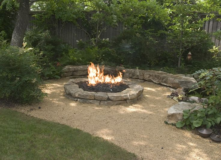This fire pit, surrounded by a crushed marble path, provides a focal point and unexpected drama to the lush garden setting. Designed using gas through lava rock.