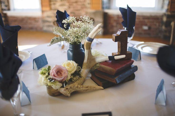 Centerpiece. Vintage books. Antler. Floral arrangements. Mason jar. Wooden table number.  Photo Credit: www.melissajohnstonphotography.com. Set up by: https://www.facebook.com/focalpointdesignsanddecor?ref=hl