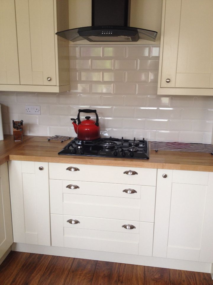 Cream subway tiles with cream kitchen and oak worktop