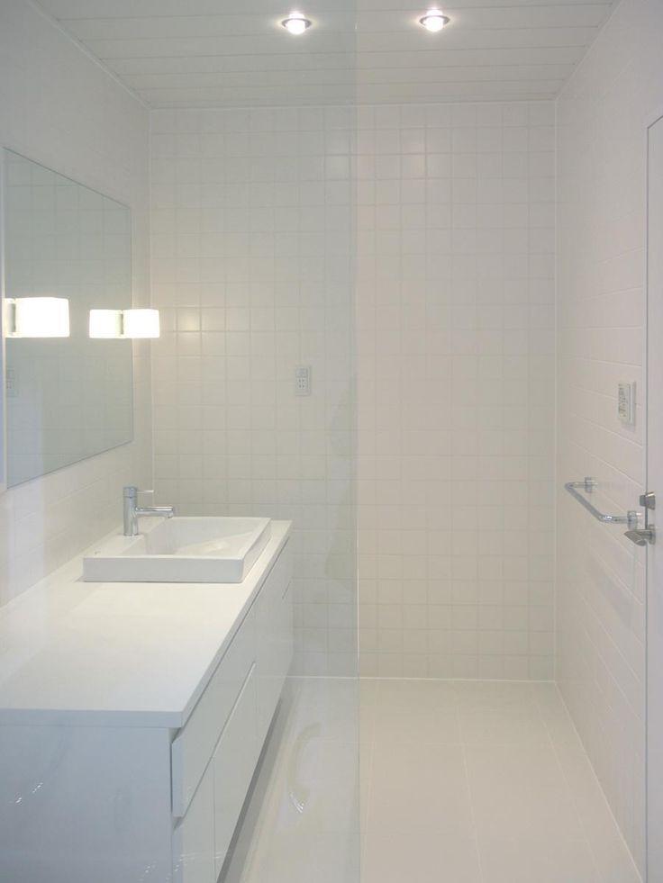 木造住宅の2階にあった洗面と浴室のリフォームです。<br /> 改修前は、洗面、浴室の広さはそれぞれ1坪で、壁と扉で仕切られていました。洗面床が長尺シート、壁がビニールクロス張り、浴室は床壁50角タイルで仕上げられた普通の洗面と浴室でした。<br /> 2階なので、一般的にはユニットバスを使うことが多いと思いますが、ここは在来工法でしたので、その点はちょっと違っていたかも知れません。<br /> <br /> ストイックに要素をそぎ落としたデザインと、ホワイトだけの空間です。<br /> 生活感を感じさせず、機能的に。オーナーの要望でもありました。<br /> <br /> 浴室と洗面の間の壁を取り払って、ガラスに変えています。ガラスは枠にはめずにスクリーンのように見える様にデザインしました。仕切りを取り払い、透明なガラスにしたことで、1坪づつの空間が2坪の空間に広がりました。 専門家:長井義紀が手掛けた戸建リフォーム・リノベーション事例:ミニマルバスルーム|木造住宅2階の洗面浴室のリフォーム|のページ。新築戸建、リフォーム、リノベーションの事例多数、SUVACO(スバコ)