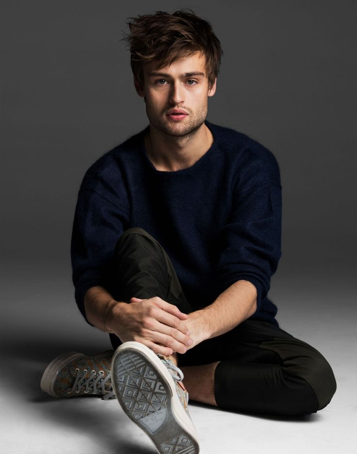 Douglas Booth sits on the ground and rests his hands on his leg