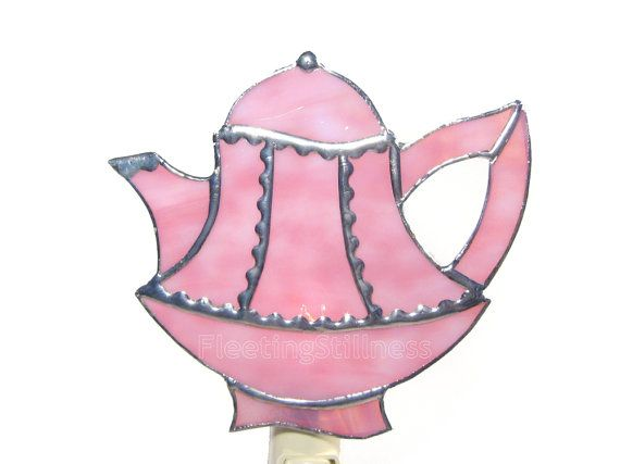 This is a teapot night light that was inspired by Victorian tea pots. The front of the night light is a stained glass panel made of tea rose pink with dark pink mottle glass. The nightlight was made using the copper foil or Tiffany style method - so no lead came was used. The seams are silver color. The stained glass panel is approximately 6 x 5.5 inches and is attached to a UL Listed Night Light with a 4 watt bulb. THIS ITEM IS MADE TO ORDER and, therefore, might differ slightly from the…