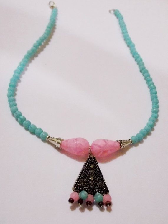 Stylish and fashionable ink and blue neon beads necklace with carved steel pendant. Also used small wooden beads. This is the best one to add to your jewelry box.