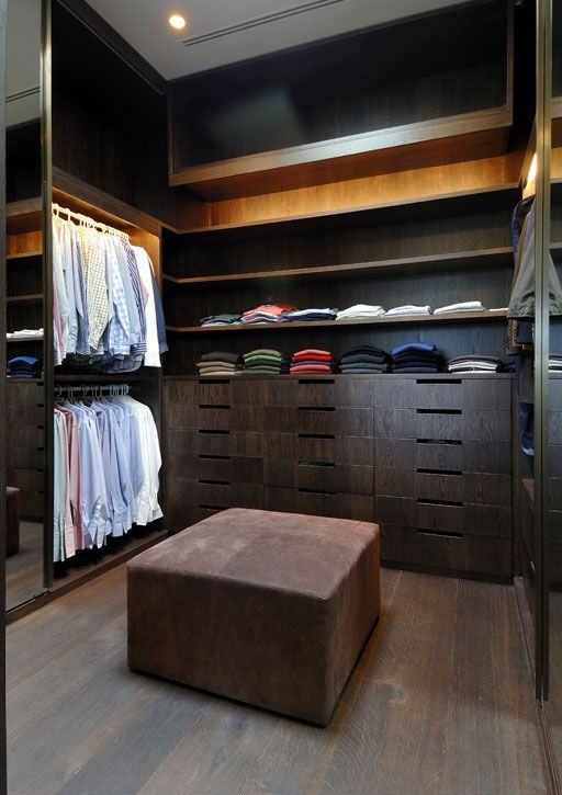 masculine closet with dark wood cabinetry, a leather tuffet and great lighting