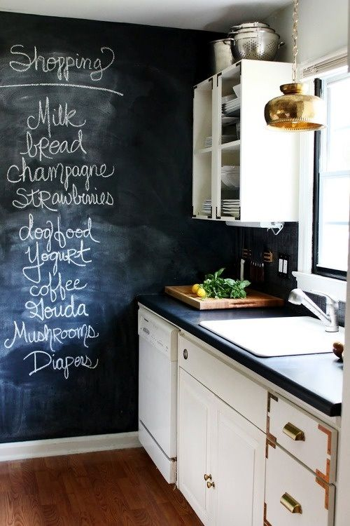 chalkboard wall in kitchen. love the contrast between the white cabinets and black wall. & that gold pendant is stunning!