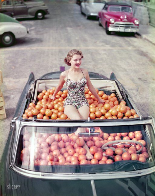 It's 1952. A swimsuit model is riding in a Cadillac convertible filled with oranges!