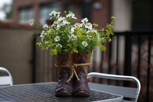 cowboy boots filled with daisies as the centerpieces.