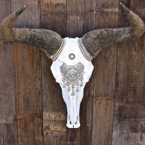 """**AFRICAN SUNRISE WILDEBEEST SKULL** >> Imported Blue Wildebeest Skull from Africa >> Silver Indian Adornment on the Forehead >> Ethiopian Nickel Bead detail around the horns. >> Mother of Pearl Shell detail on the top and bottom of design. >> Widest Part of Horn to Horn 22"""" >> Highest point of horn to bottom of the skull 23"""""""