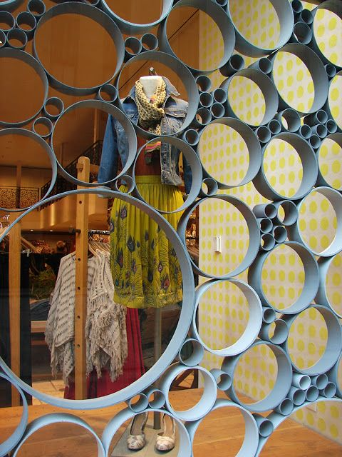 Cute idea for room divider or back of a craft show booth display. Bigger tubes could feature a handback, necklace or pair of shoes. Smaller tubes could show earrings or bracelets. Think about how you could even suspend the work inside the center of the tube. No big deal with thread or monofilament. Window from anthropologie but I have seen the same idea in Nordstrom's.
