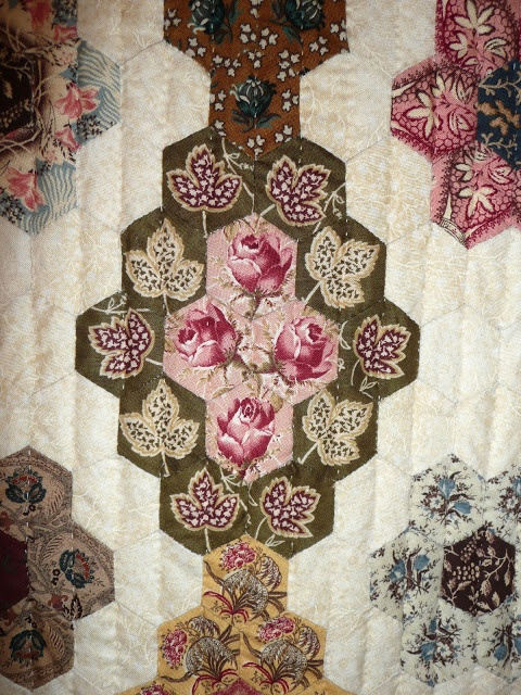 Diamonds with Flowers (Losanges de fleurs) was made by Dominique Husson from Arvert, France.  It was inspired by an American quilt (circa 1840).  The flowers each are centered in one-inch hexagons.  Yes -- there are many more hexagons in this exhibit!