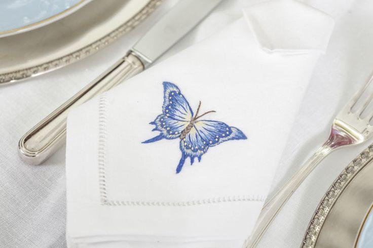 Para compor a mesa, guardanapos em linho bordados à mão em 4 cores diferentes, descansos de talher e marcadores de lugar em formato de borboleta em prata. Ainda em prata, talheres e sousplat completaram a mesa.