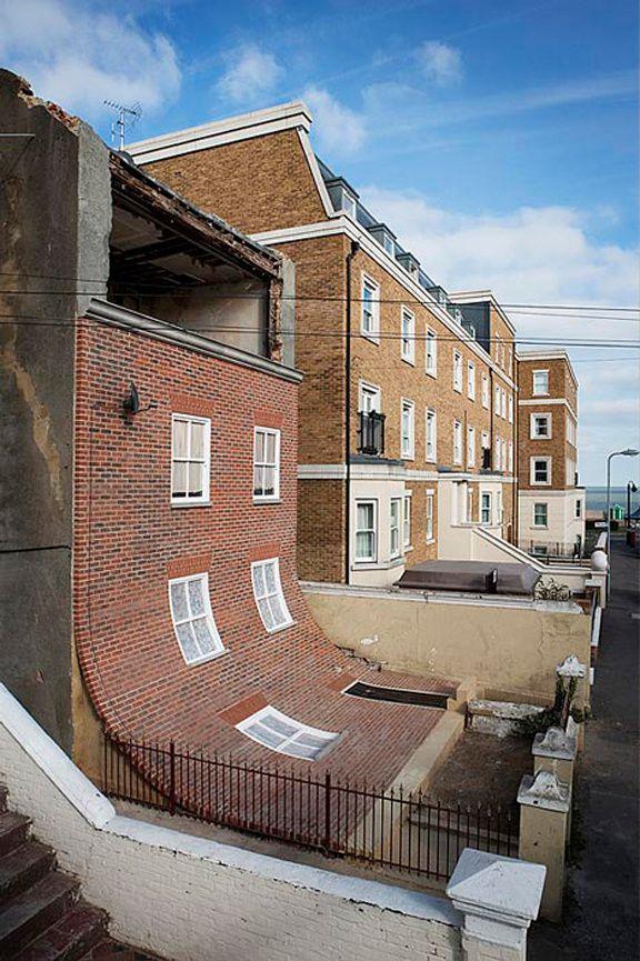 L'architecture fantaisiste d'Alex Chinneck. Lentement, la façade de brique se détache de cette maison située à Margate, de l'autre côté de la Manche, et glisse sur l'asphalte, dévoilant le désordre à l'intérieur... Le designer Alex Chinneck nous fait rire avec cette vision fondante de l'architecture qu'il a appeléeFrom the Knees of my Nose to the Belly of my Toes(«Des genoux de mon nez au ventre de mes orteils»)