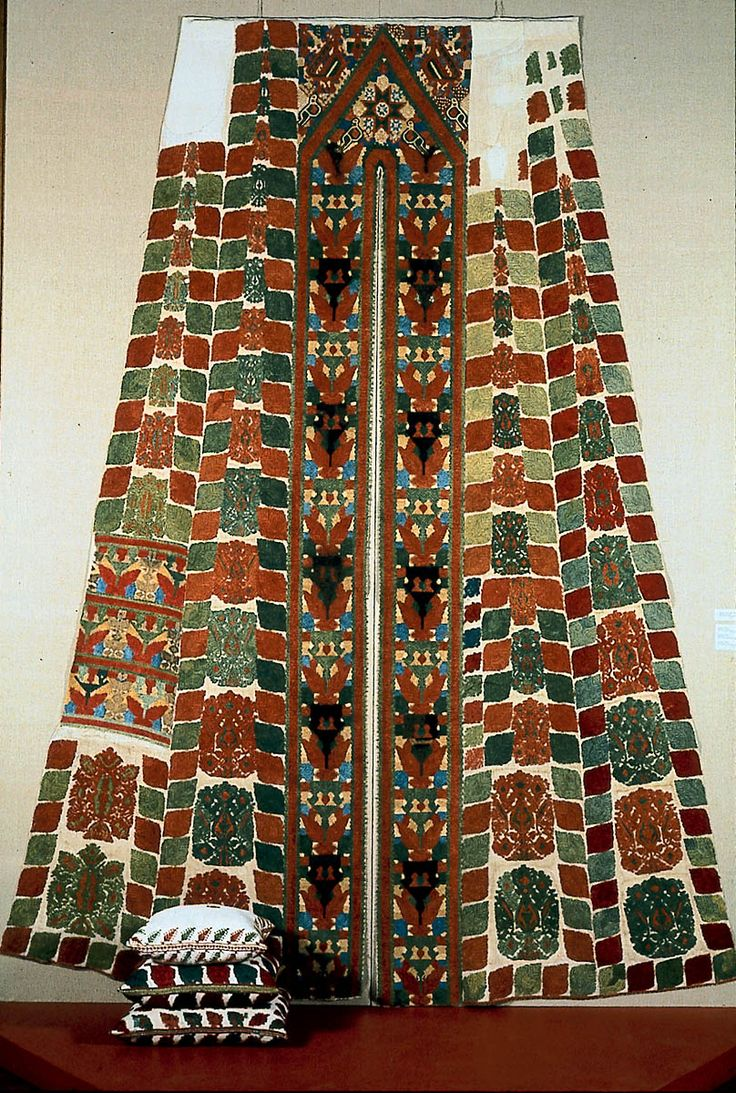 """Doorway of a bed tent Greek (Dodecanese, Cos) 18th or 19th century Dodecanese, Island of Kos, Greece  Silk embroidery on linen Eight tapering linen panels embroidered with polychrome silk yarns. Design of six outer panels shows repeating """"Queen"""" patterns, alternating red and green; central panels embroidered with King and Queen pattern, and small birds; """"gable"""" of central archway repeats these patterns and adds variety of birds; and double-headed eagles. www.mfa.org"""