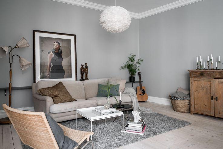 гостиная серые стены перьевая лампа потолочный карниз бежевый диван гитара комод корзина подсвечники торшер