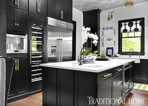 painted black cabinets with simple shakerstyle doors are accented with hefty hardware in this showhouse kitchen