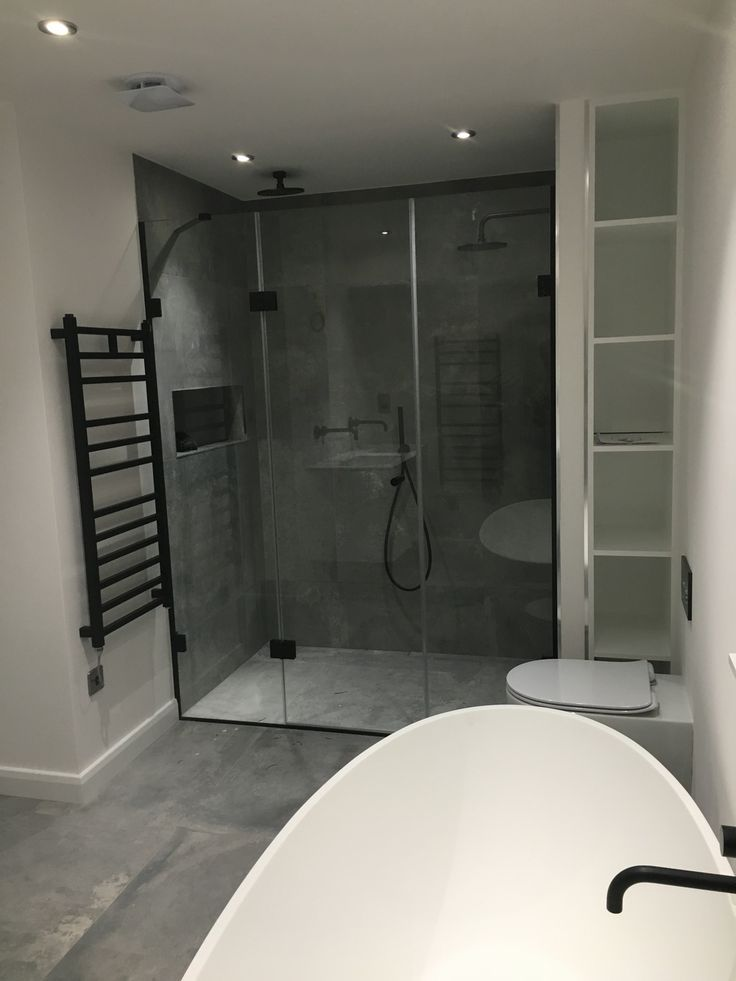 Minimal bathroom design with a grey stone double shower, matt white stone freestanding bath with matt black taps and features