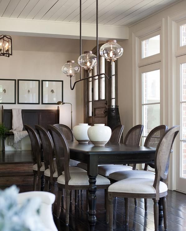 French sunken dining room boasts a plank ceiling accented with a 3 light linear vintage pendant illuminating a black dining table with turned legs lined with cane back dining chairs.