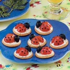 Ladybug snacks - cherry tomatoes cut on top of crackers and cheese spread. Topped off with olives.