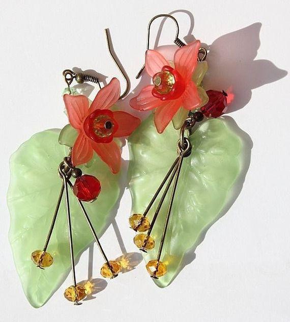 Boucles d'oreilles en bronze et verre composées d'une fleur rouge en lucite posée sur une large feuille verte