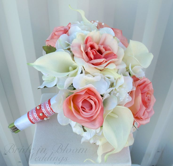 """An elegant coral wedding bouquet designed with 12 white real touch calla lilies, pretty coral roses, on a bed of creamy white hydrangea, pearl loops throughout. Handle treatment is wrapped with white & coral satin ribbon with a white lace sash & pearl pins to finish. Pictured bouquet measures: 10"""" ( 25 cm ) wide x 12"""" ( 30 cm ) tall."""