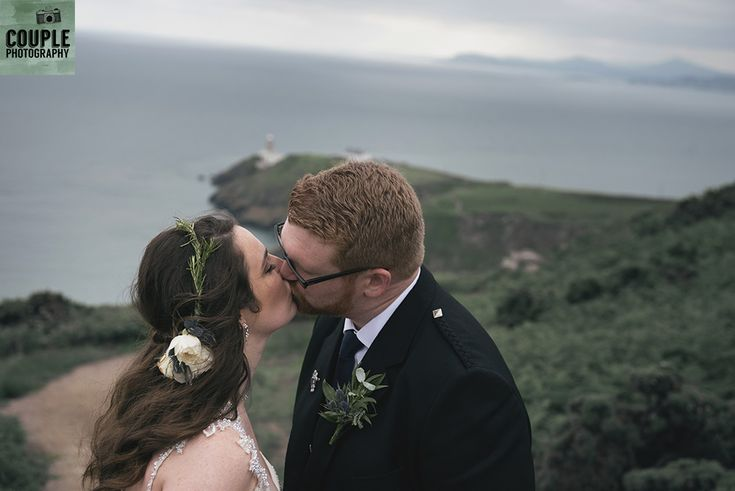 The bride & groom kiss by the Howth Cliffs. Wedding in The Abbey Tavern, Howth. Photographed by Couple Photography.
