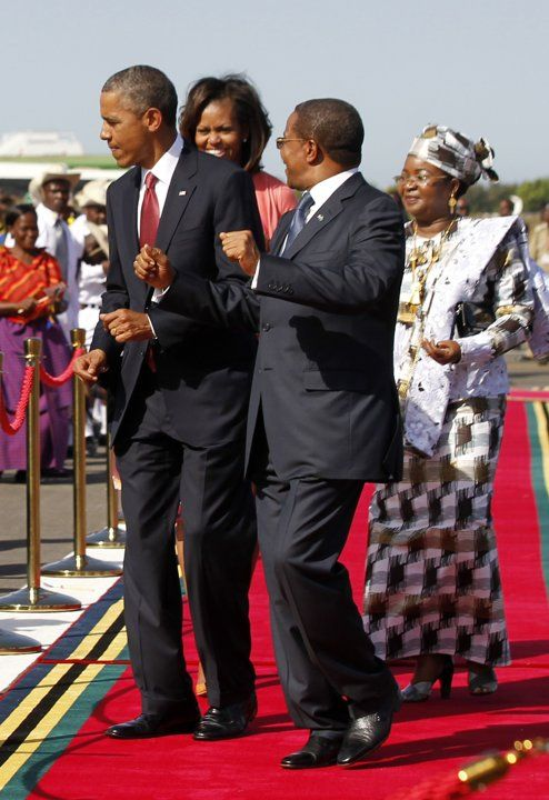 U.S. President Obama dances to the music of a Tanzanian band with Tanzanian President Kikwete, at an official arrival ceremony for Obama at Julius Nyerere Airport in Dar es Salaam
