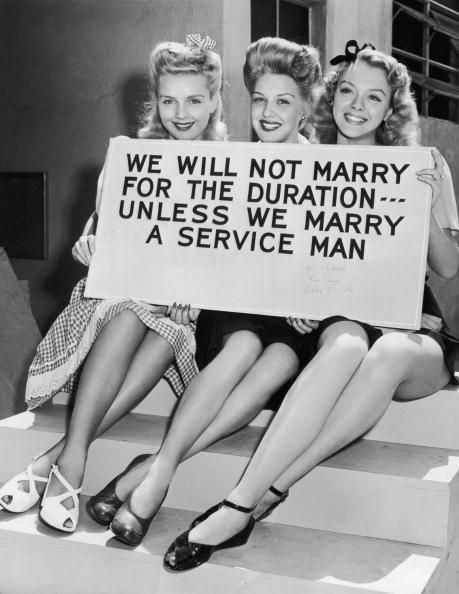 circa 1943: Three young blonde women hold a sign which reads, 'We will not marry for the duration - unless we marry a service man'. (Photo by Hulton Archive/Getty Images)