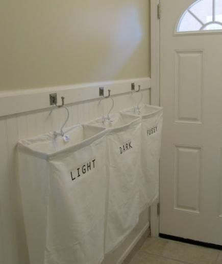 """This clever project is easy to execute and solves two problems: sorting laundry and conserving floor space in a small laundry room. Simply hang canvas bags from sturdy wall hooks. Label each one """"lights, darks, and delicates"""" or, if you prefer, designate one bag to every family member."""
