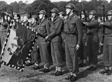 Standard guard of infantry battalion. Czechoslovak soldiers after retreat from France are still equipped with French M26 helmets. Great Britain, Cholmondeley camp, 1940.