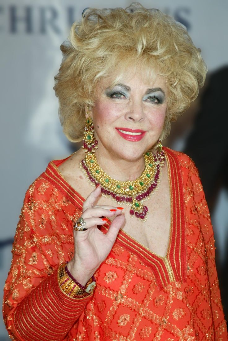 Elizabeth wearing  rubies, gold and emeralds at Christies auction house in 2002.