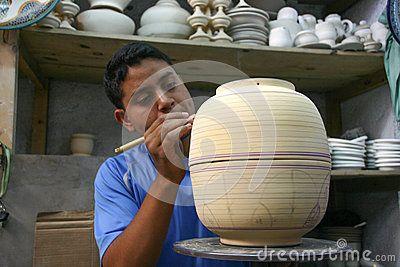 Boy draws a ceramic pot in a factory.