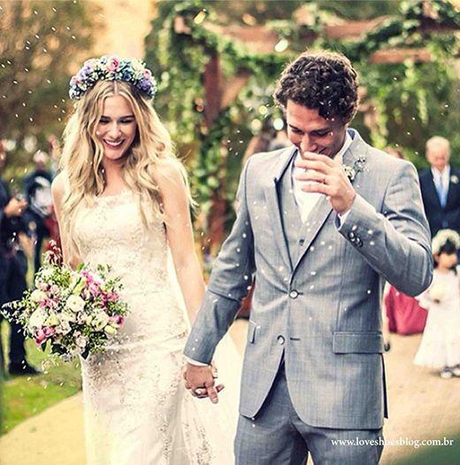 Casamento no campo de Fiorella Mattheis e Flávio Canto. A noiva usa tiara de flores lilás e rosa e leva buquê de flores rosa e branca. O noivo usa terno cinza, apropriado para o casamento realizado durante o dia.